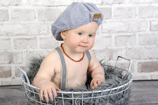 Baby mit Mütze und Hosenträger