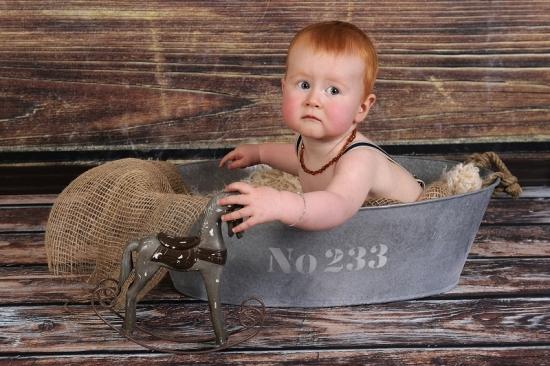 Rothaariges Baby schaut erschreckt aus Eisenwanne