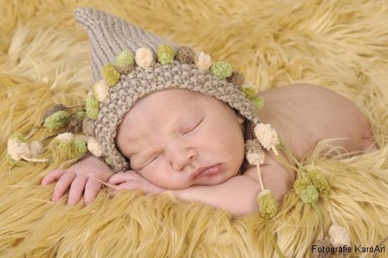 Neugeborenes Baby mit einer Mütze in einem Fell